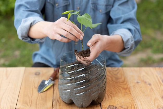 플라스틱 냄비에 식물을 들고 사람