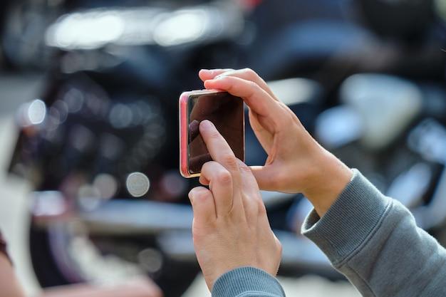 スマートフォンを持って路上で写真を撮る人。