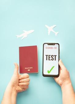 파란색 배경 여행 개념에 대한 covid 테스트와 여권을 보여주는 스마트폰을 들고 있는 사람