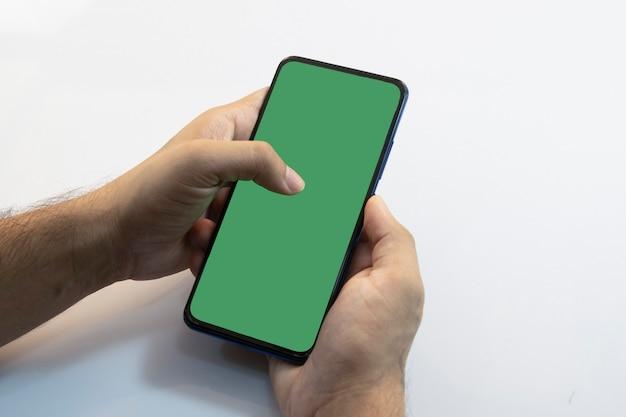 Человек, держащий смартфон с зеленым экраном