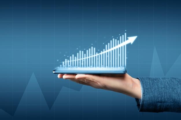 ビジネスの成長と利益のグラフが付いたタブレットを持っている人。