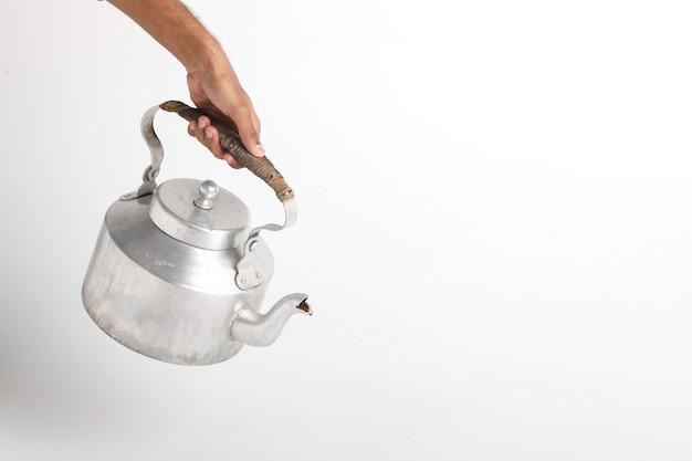 Person holding aluminum tea kettle on white surface
