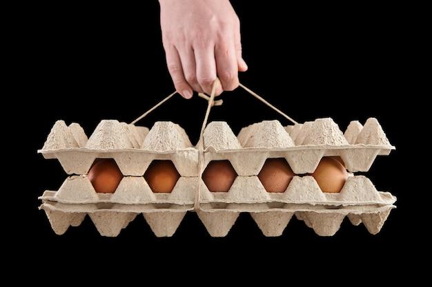 黒で隔離の卵トレイを持っている人