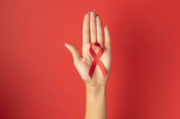世界エイズデーのリボンのシンボルを持っている人