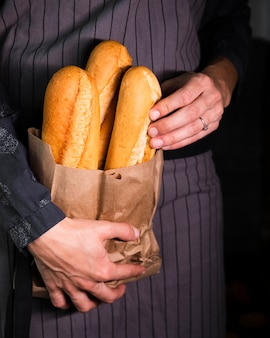 Person holding bag with baguettes