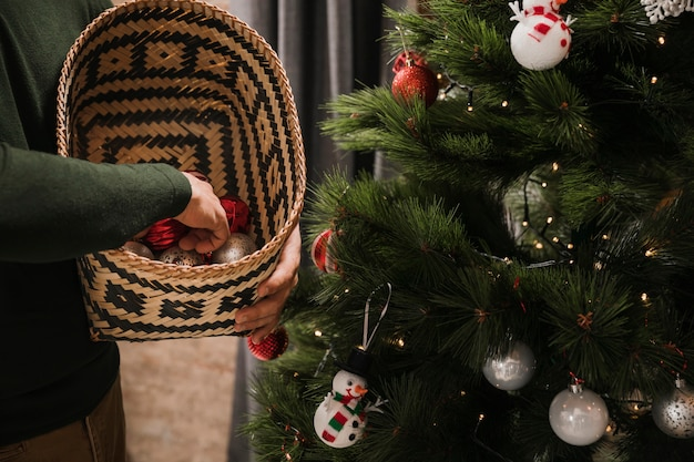 Person holding basket with christmas tree