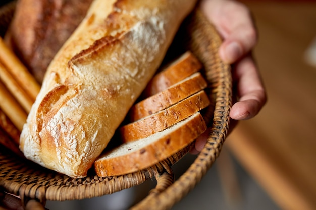 Person holding basket with various breads freshly baked