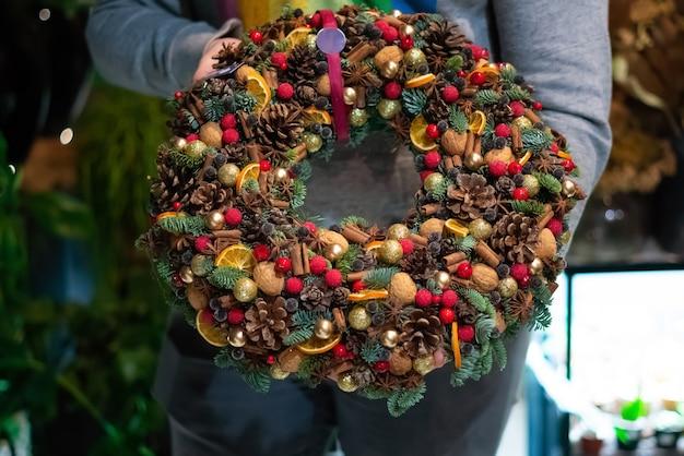 Человек, держащий красивый и красочный рождественский венок ручной работы, зеленые еловые ветки, украшенные сосновыми шишками и другими украшениями. рождественский венок в руках.