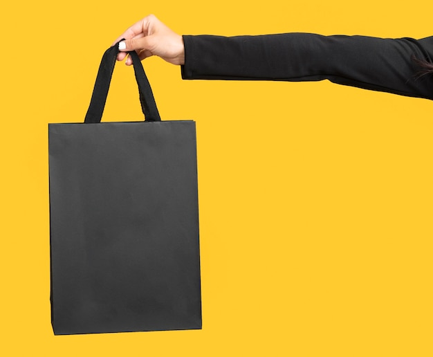 Person holding big black shopping bag copy space