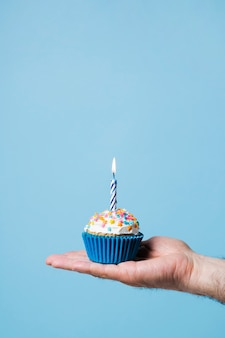Person holding birthday cupcake with candle