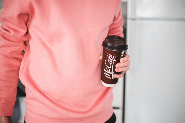 Человек, держащий черно-белую одноразовую чашку