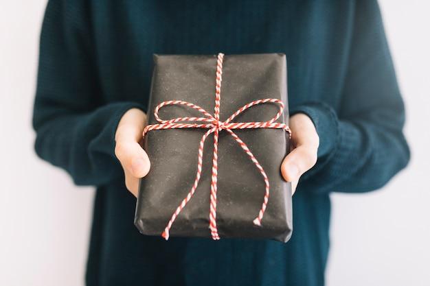 Persona che tiene il contenitore di regalo nero in mano