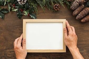 Person holding blank frame on table