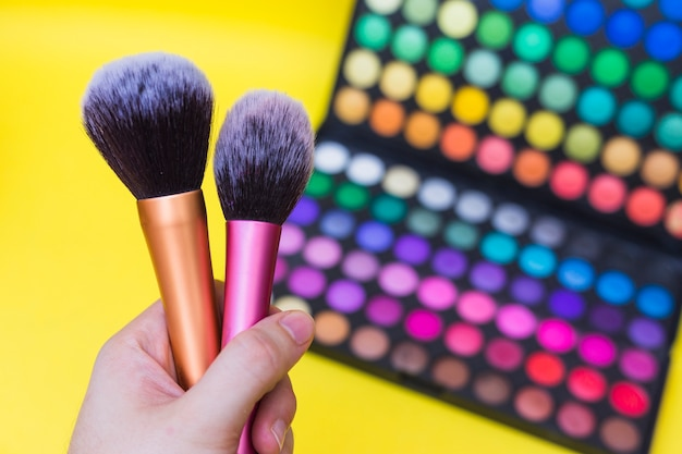 A person holding blusher makeup brush in front of eyeshadow palette against yellow background