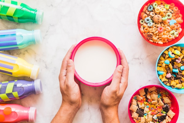 Person holding bowl with milk on table