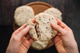 Person holding broken cookie in hands