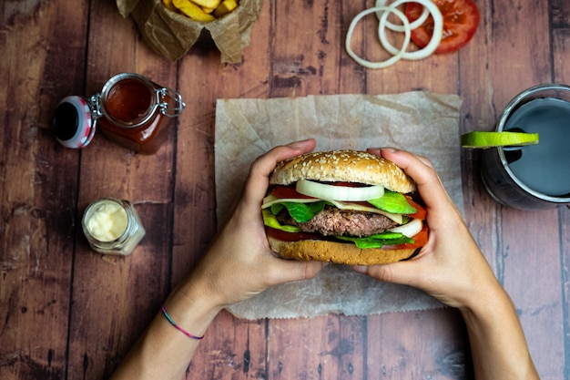 Person holding a burger with fries, onion rings and tomato on wooden table