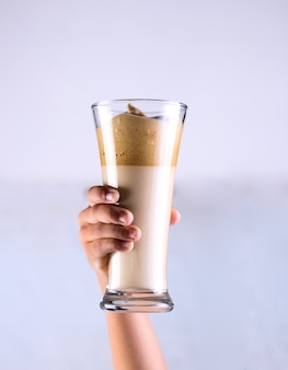 Person holding caramel smoothie in a glass behind a white wall