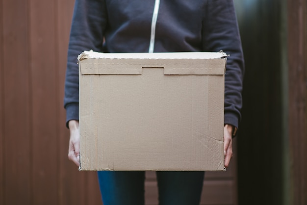 Person holding a cardboard box