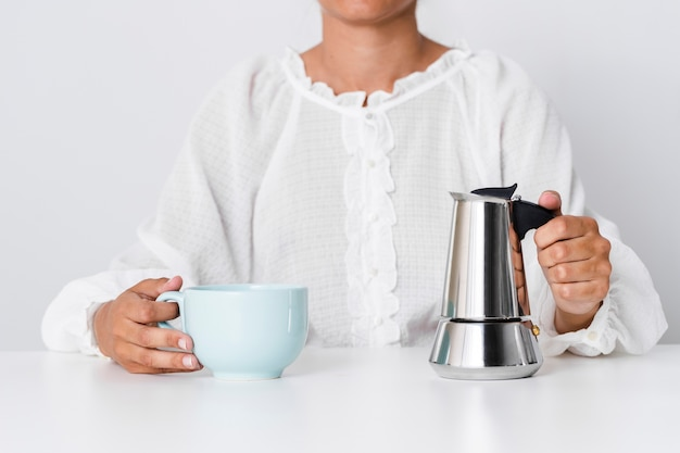 Person holding ceramic mug and kettle