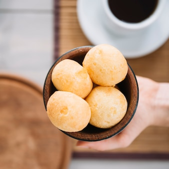 Person holding cheese balls in wooden bowl