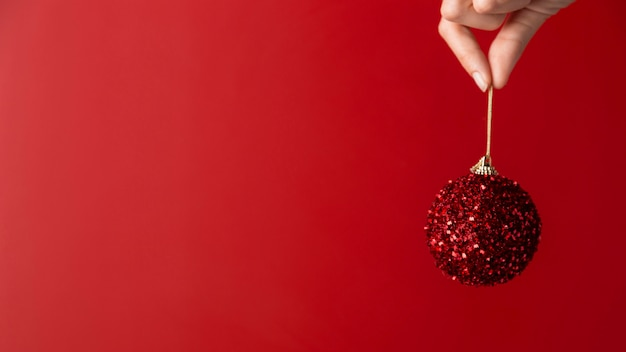 Person holding christmas ball copy space