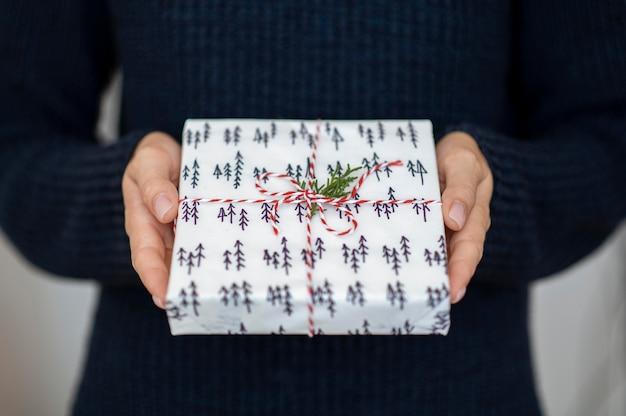 Лицо, держащее рождественский подарок с конфетами и листом