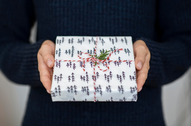 Persona in possesso di regalo di natale con stringa di caramelle e foglia