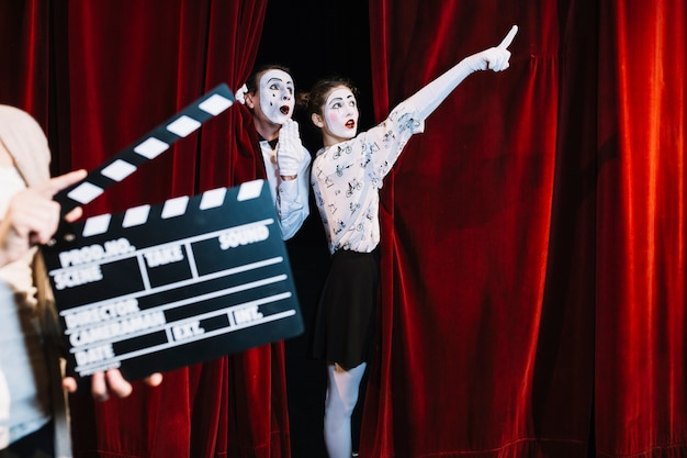 A person holding clapper board in front of male mime looking at female mime pointing somewhere