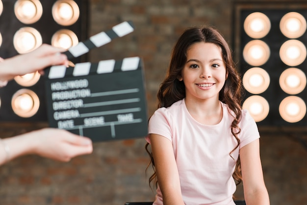 A person holding clapper board in front of smiling girl