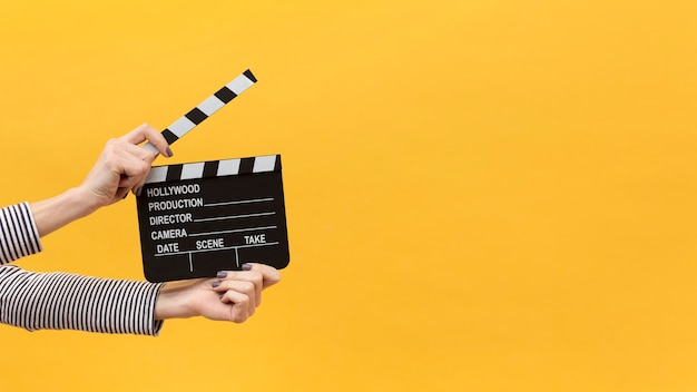 Person holding a clapper board on yellow background