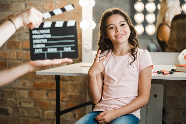 A person holding clapperboard in front of girl showing peace sign