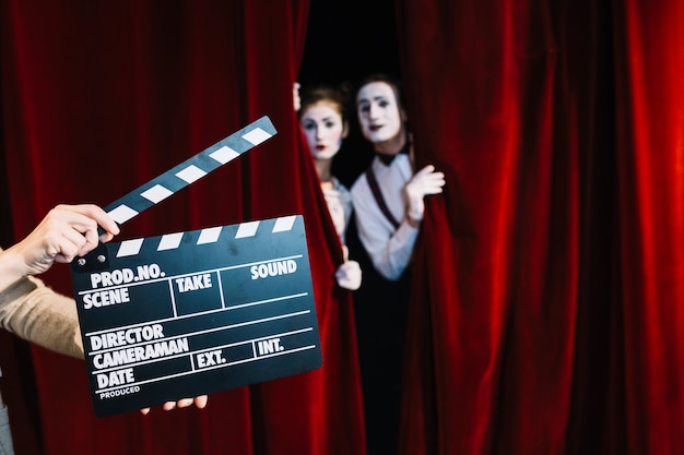 A person holding clapperboard in front of mime couple standing behind the red curtain