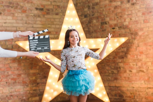 A person holding clapperboard in front of smiling girl shrugging