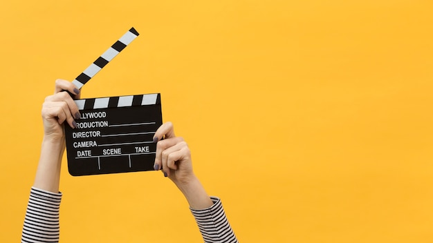 Person holding a clapperboard with copy space