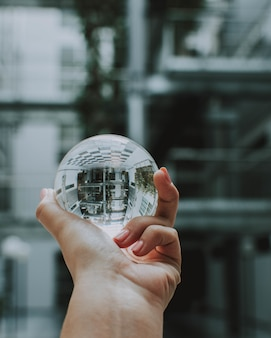 A person holding a clear crystal glass ball with the reflection of a building