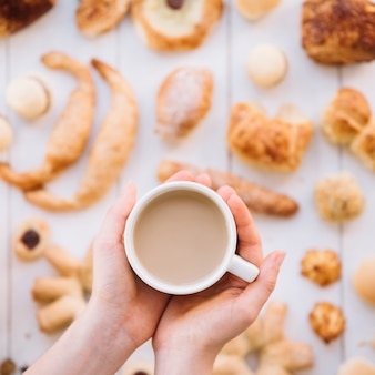 Person holding coffee cup in hands above bakery