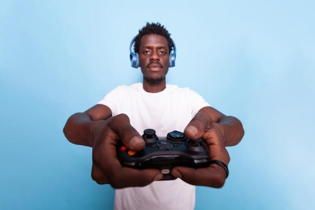 ヘッドホンをつけたままビデオゲームのコントローラーを持っている人