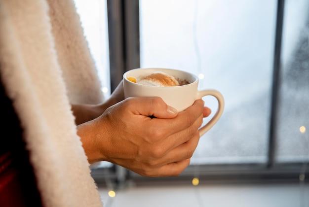 Persona in possesso di una tazza di cioccolata calda