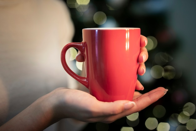 Person holding a cup with christmas background