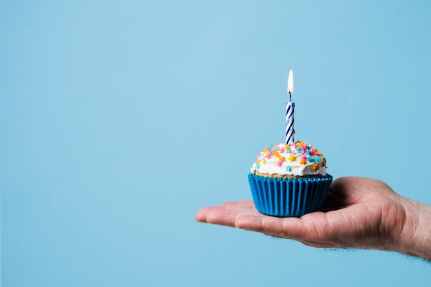 Person holding cupcake with lit candle