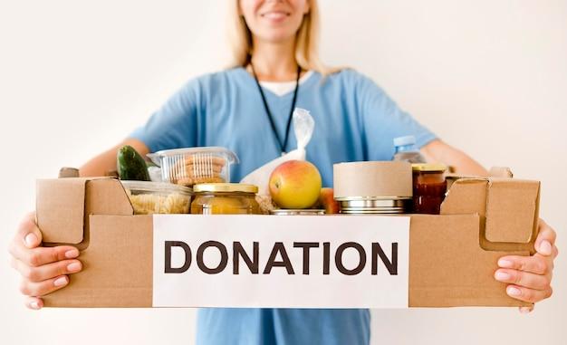 Persona che tiene la scatola di donazione con il cibo