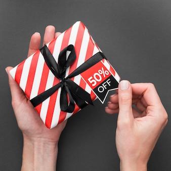 Persona in possesso di confezione regalo con etichetta di prezzo
