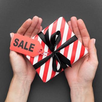 Persona in possesso di confezione regalo con etichetta di vendita