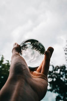 A person holding a glass ball with the reflection of beautiful green trees and breathtaking clouds