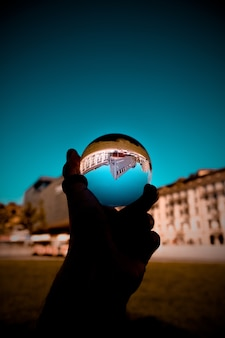 A person holding a glass ball with the reflection of buildings and the blue sky