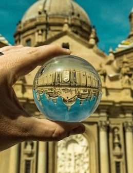 A person holding glass ball with an upside-down reflection of saint petersburg, russia