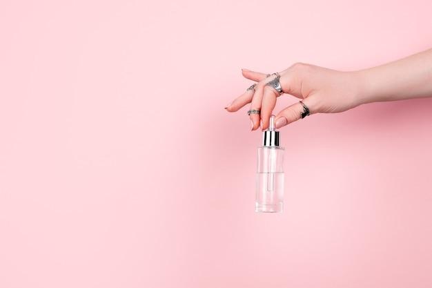 ピンクの破れた紙を通してガラス瓶を持っている人