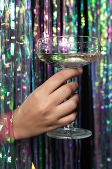 Person holding a glass of champagne front view