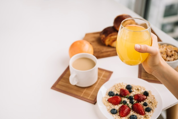 Person holding glass of juice above oatmeal on table
